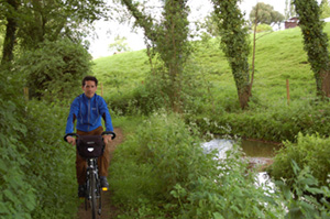 Daniel Coward rides through Dodford on the road that is a river, through the village once former home of Patrick Leigh Fermor